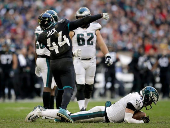 Jacksonville Jaguars linebacker Myles Jack (44) reacts after sacking Philadelphia Eagles quarterback Carson Wentz (11), right, during the second half of an NFL football game at Wembley stadium in London, Sunday, Oct. 28, 2018. (AP Photo/Matt Dunham)
