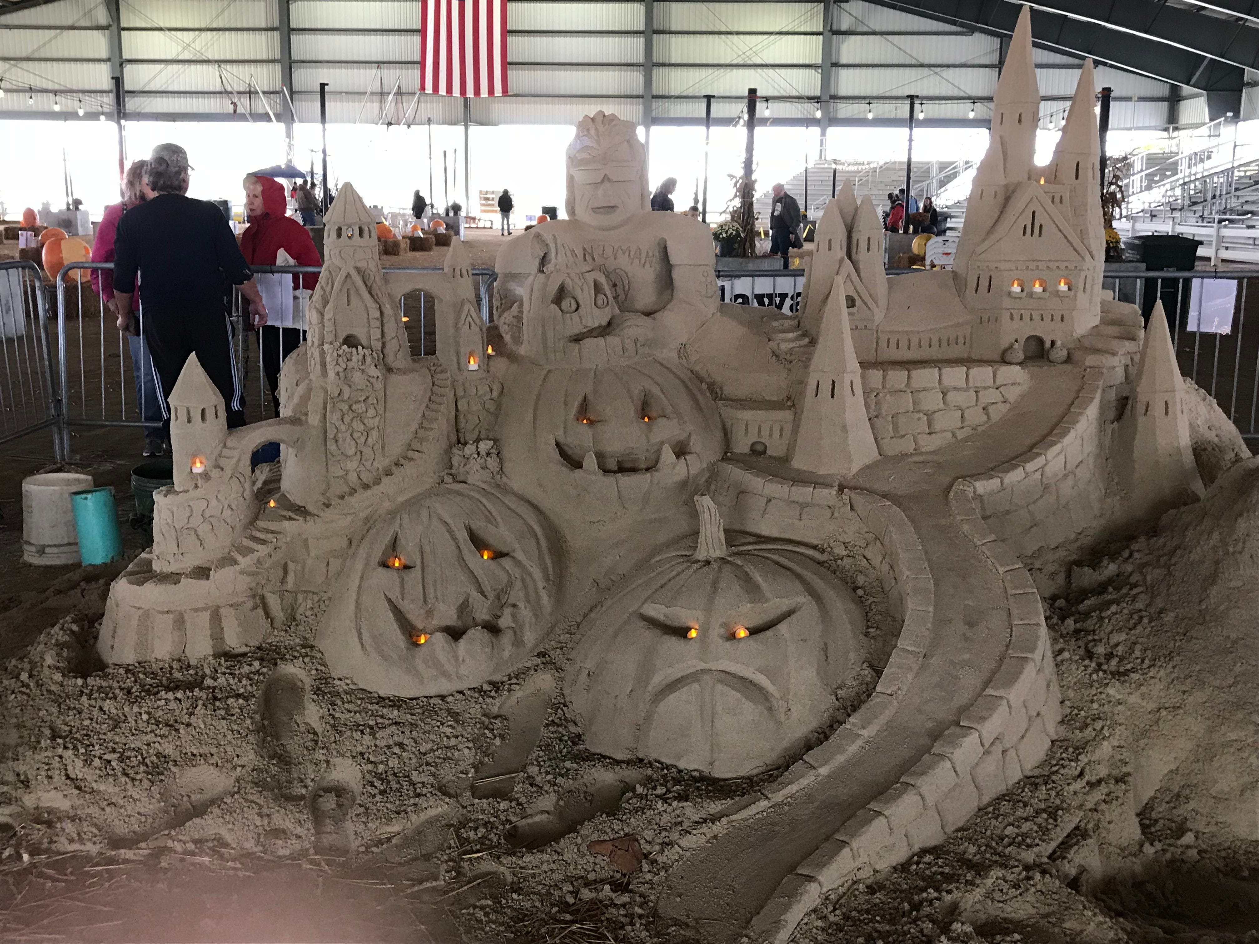 Andrew West, in the rear talking to guests, created a Halloween sand sculpture at the first Great Delaware Pumpkin Carve.
