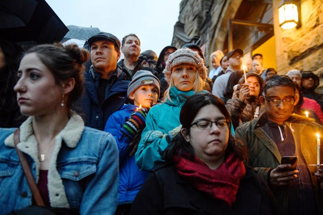 People stand on the stairs of Sixth Presbyterian Church as the crowd spills up the hill and down the street for a vigil blocks from where an active shooter shot multiple people at Tree of Life Congregation synagogue on Saturday, Oct. 27, 2018, in the Squirrel Hill section of Pittsburgh.