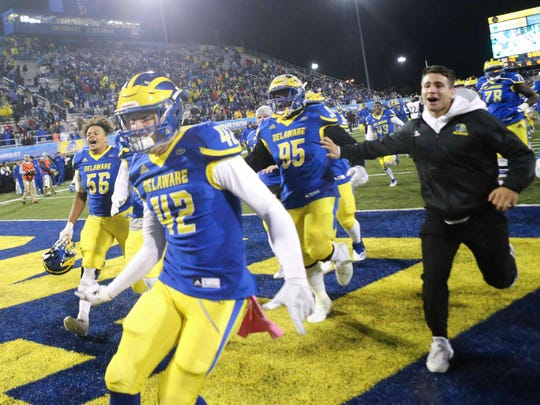 Delaware begins a celebration after the final Towson pass play was broken up as time expired in the Blue Hens' 40-36 win at Delaware Stadium Saturday.