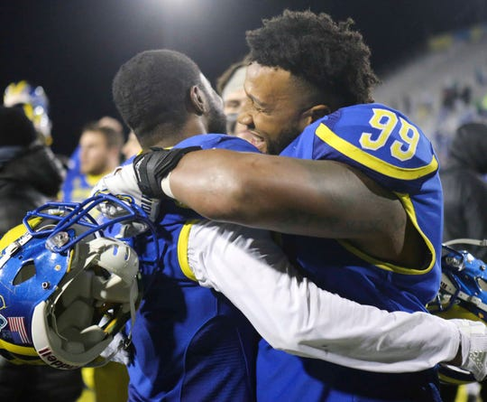 Delaware's Malcolm Brown (left) and Cam Kitchen celebrate the Blue Hens' 40-36 win against Towson at Delaware Stadium Saturday.