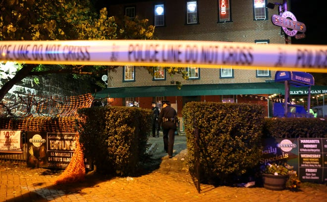Police investigate the front patio area of Kelly's Logan House in Trolley Square after reports of gunfire there at the conclusion of the city's Halloween Loop early Sunday. There were no immediate reports of injuries.
