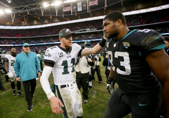 Philadelphia Eagles quarterback Carson Wentz (11), left, greets Jacksonville Jaguars defensive end Calais Campbell (93) after an NFL football game at Wembley stadium in London, Sunday, Oct. 28, 2018. The Eagles won the match 24-18.
