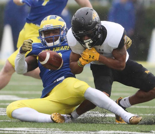 Delaware defensive back K.C. Hinton strips the ball from Towson's Shane Leatherbury but the ball slips out of bounds in the first half at Delaware Stadium Saturday.