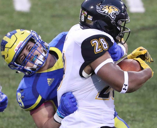 Delaware's Troy Reeder drags Towson's Yeedee Thaenrat to the ground deep in Tiger territory in the third quarter of the Blue Hens' 40-36 win at Delaware Stadium in 2018.