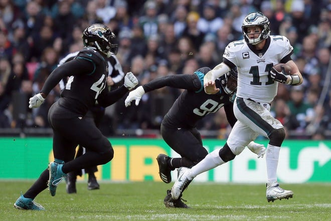 Philadelphia Eagles quarterback Carson Wentz (11), right, scrambles during the first half of an NFL football game against Jacksonville Jaguars at Wembley stadium in London, Sunday, Oct. 28, 2018. (AP Photo/Tim Ireland)