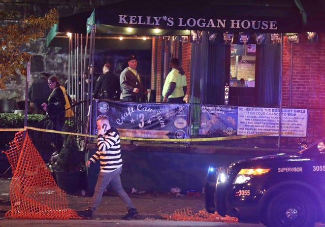 Workers begin the after-party cleanup as Wilmington police investigate a report of gunfire at Kelly's Logan House in Trolley Square at the conclusion of the city's Halloween Loop early Sunday.