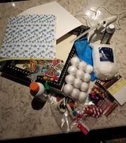 Materials needed for a holiday shadowbox include: shadowbox frame; fabric (optional); flat Christmas ornaments of your choice and printed scrapbook paper or wrapping paper.