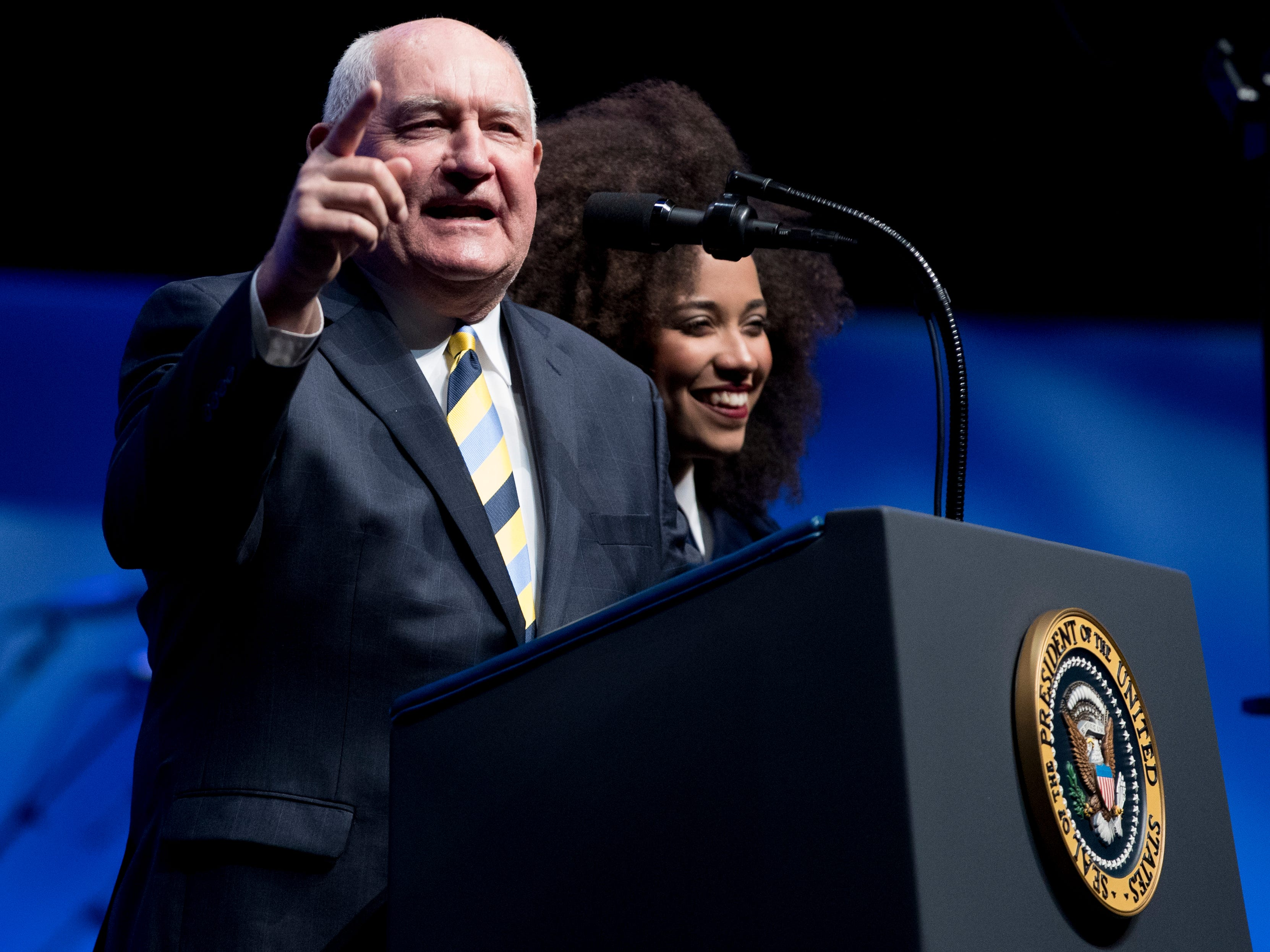 Agriculture Secretary Sonny Perdue, accompanied by Future Farmers of America President Breanna Holbert, right, speaks before President Donald Trump at the 91st Annual Future Farmers of America Convention and Expo at Bankers Life Fieldhouse in Indianapolis, Saturday, Oct. 27, 2018. (AP Photo/Andrew Harnik)