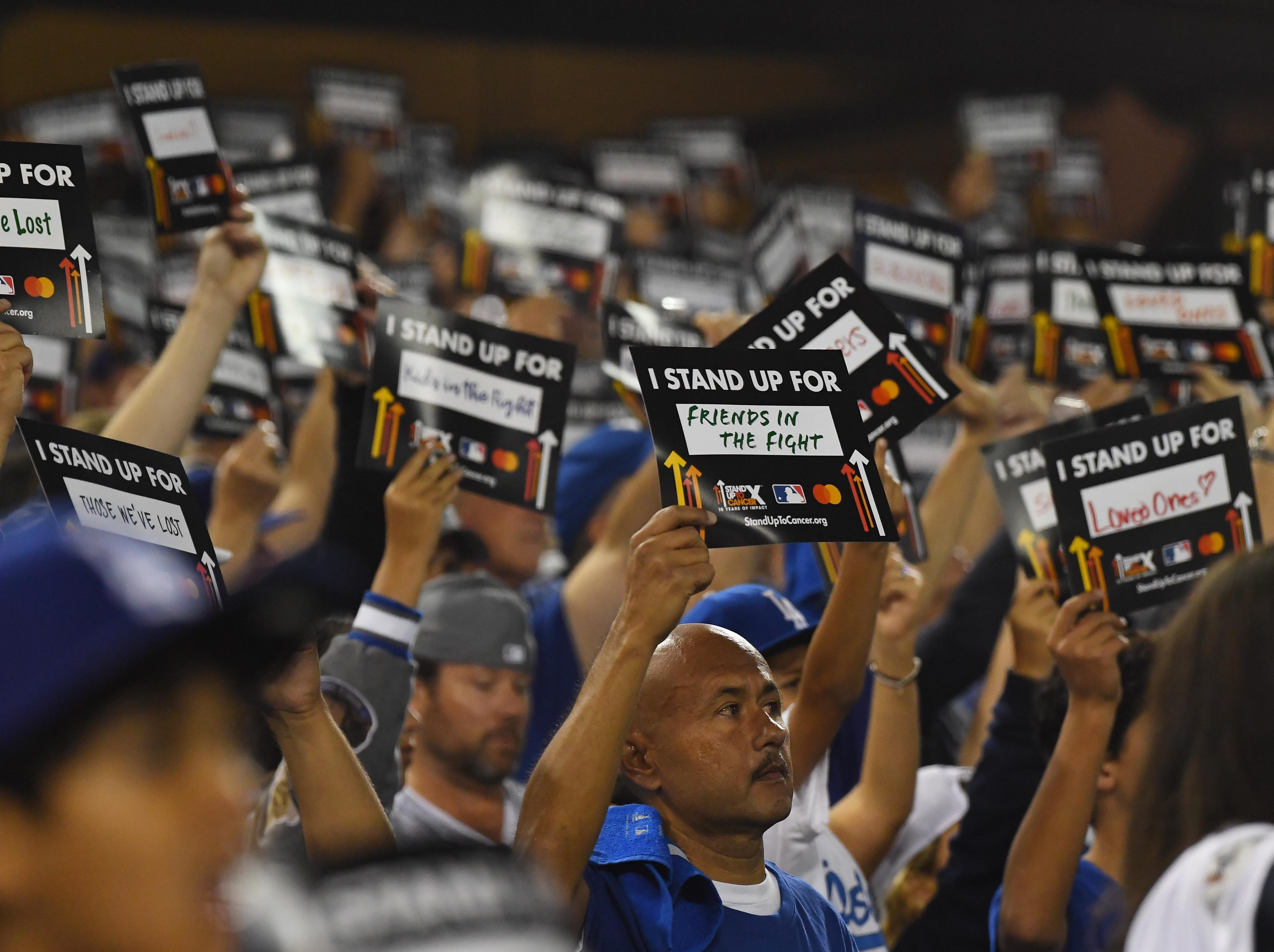 "Game 4 at Dodger Stadium: Fans hold ""Stand Up To Cancer"" signs."