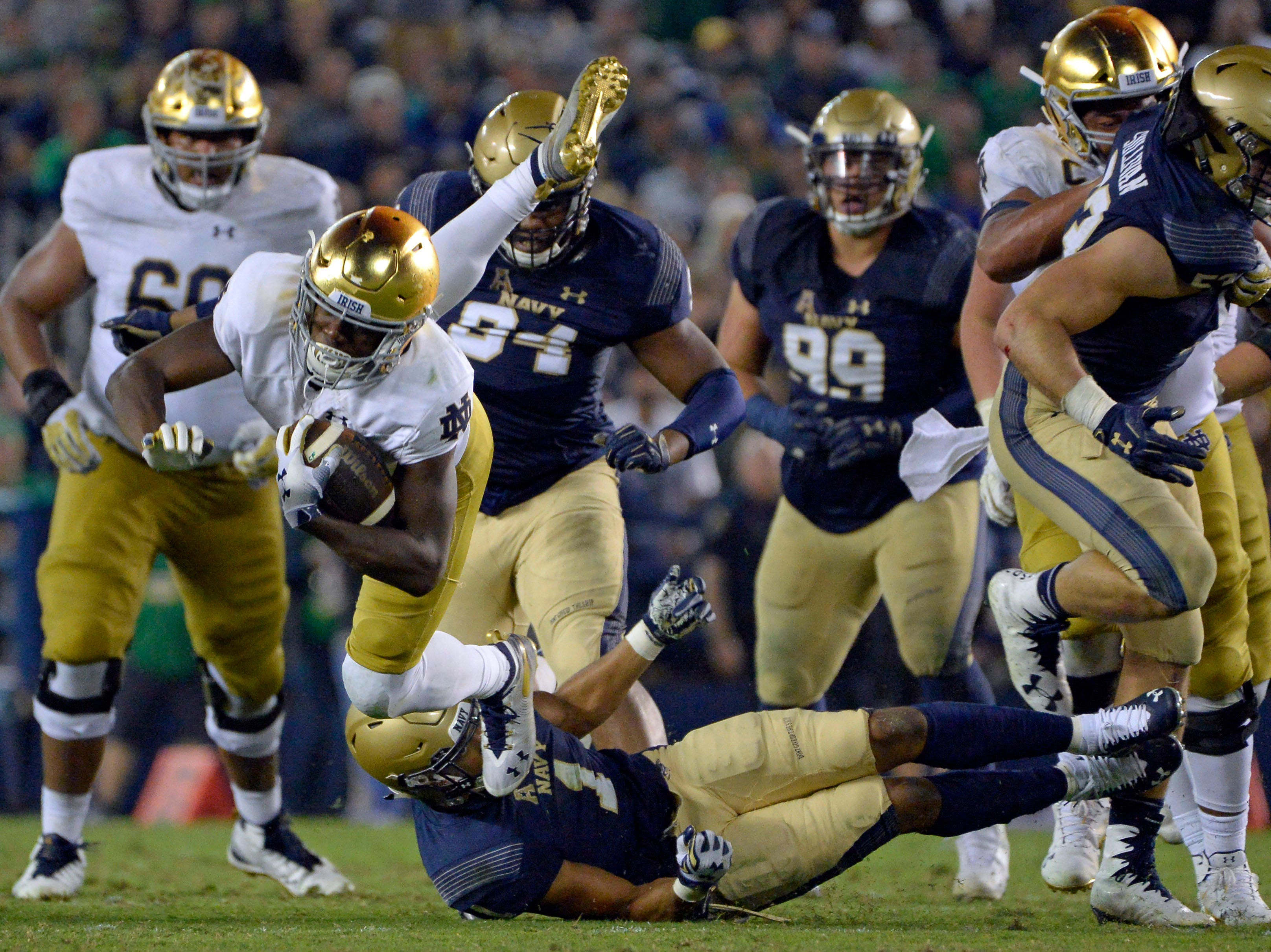 Notre Dame Fighting Irish wide receiver Jafar Armstrong (8) is tripped up by Navy Midshipmen safety Jacob Springer (1) during the fourth quarter at SDCCU Stadium.