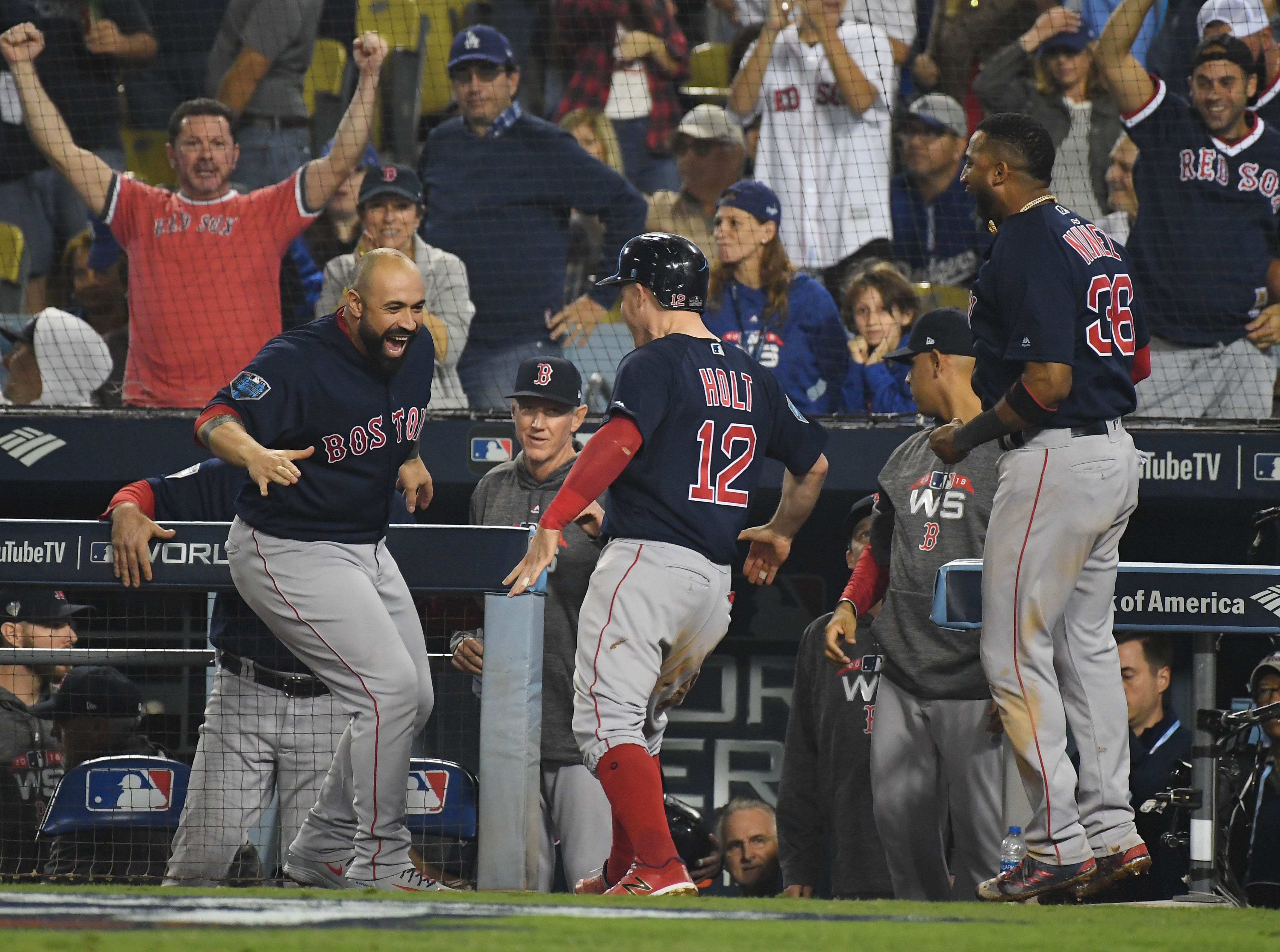 Game 4 at Dodger Stadium: Red Sox players celebrate after Brock Holt scored in the top of the ninth.