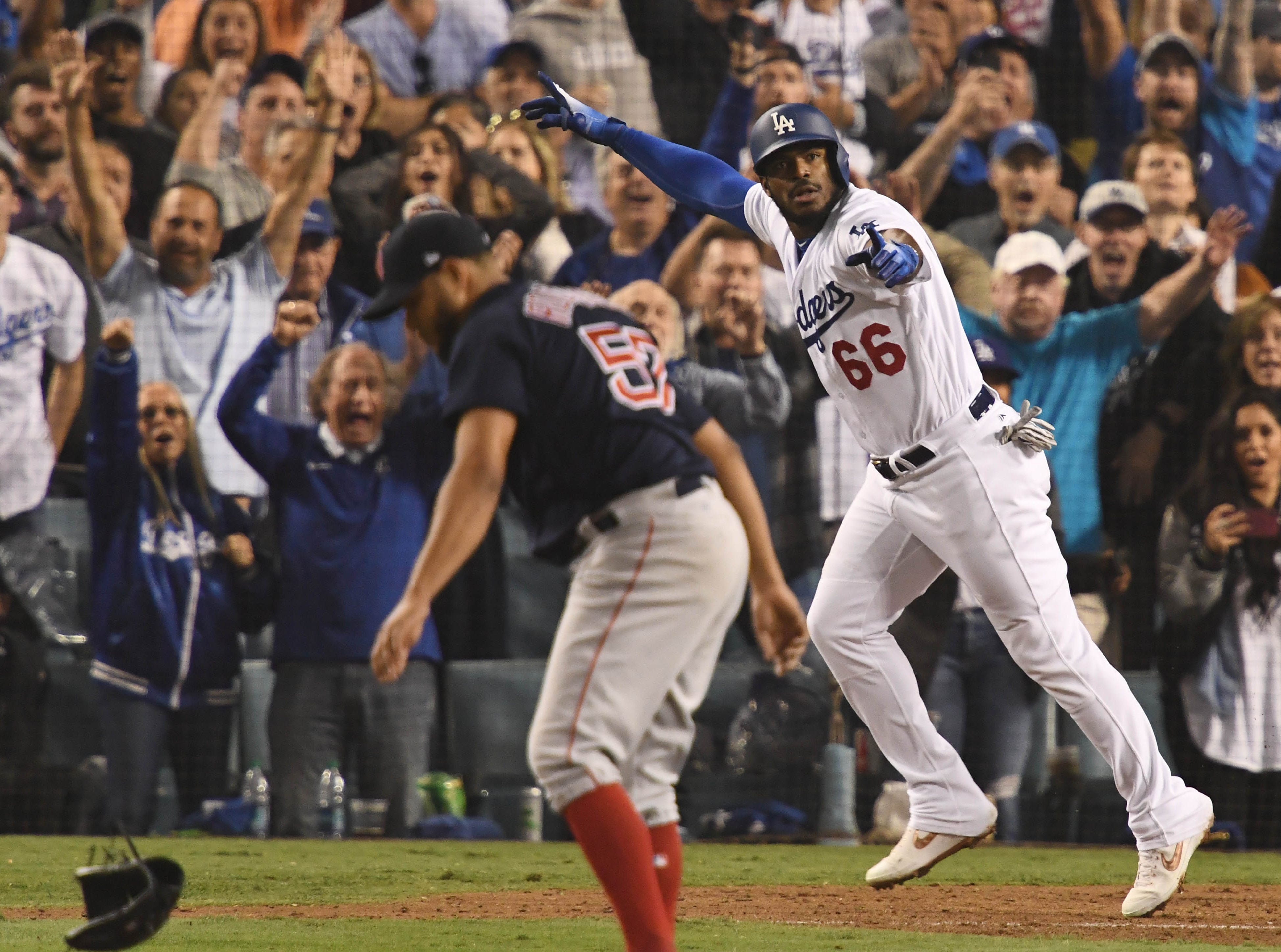 Game 4 at Dodger Stadium: Yasiel Puig celebrates his three-run homer in the sixth while Red Sox pitcher Eduardo Rodriguez spikes his glove.
