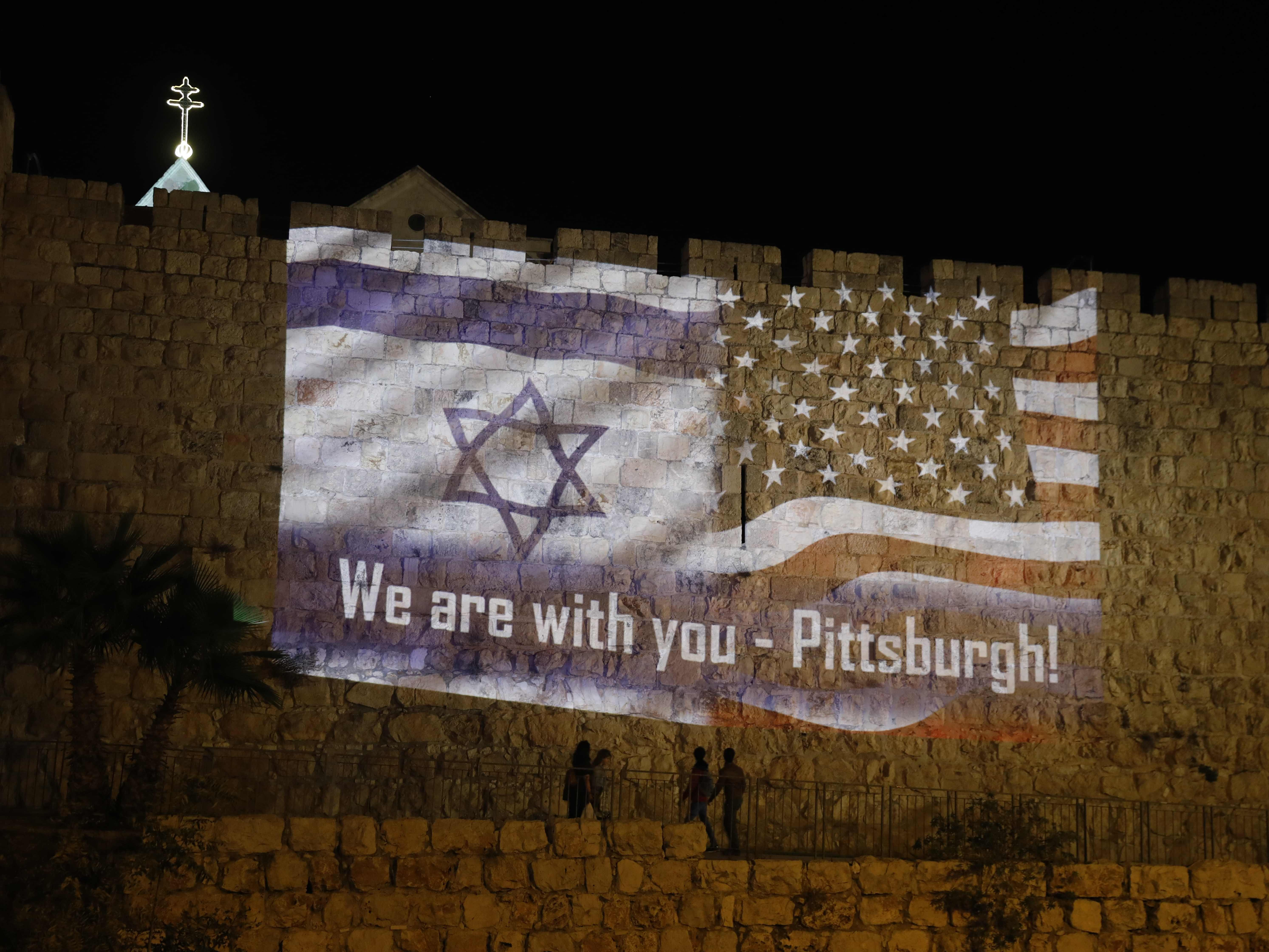People walk under the U.S. and Israeli flags projected on the walls of Jerusalem old city, Oct. 28, 2018, organized by the Jerusalem municipality to show solidarity with the Pittsburgh Jewish community following the shooting attack at the Tree of Life Synagogue in Pittsburgh.
