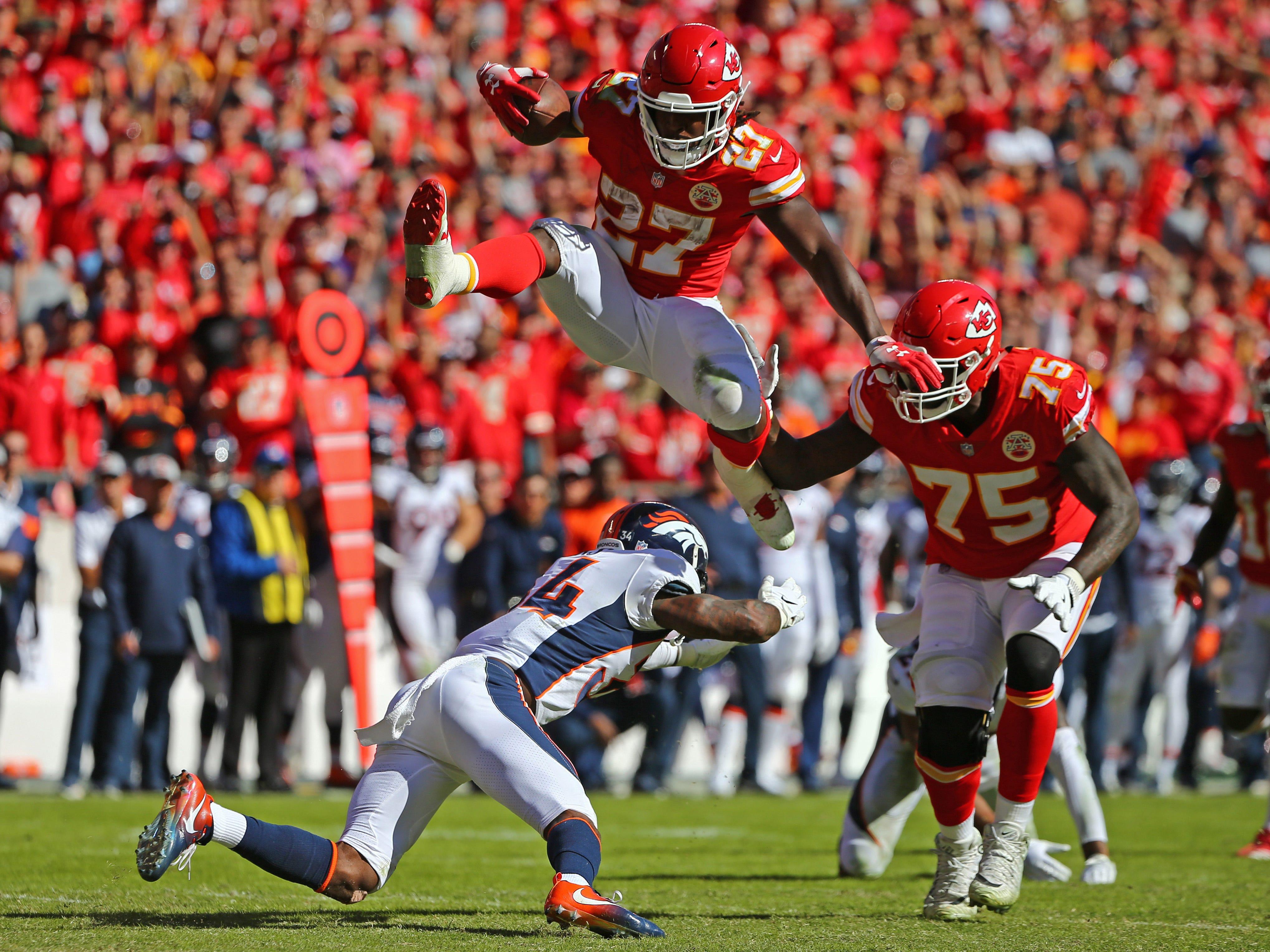 Kansas City Chiefs running back Kareem Hunt (27) hurdles Denver Broncos safety Will Parks (34) in the second half at Arrowhead Stadium.
