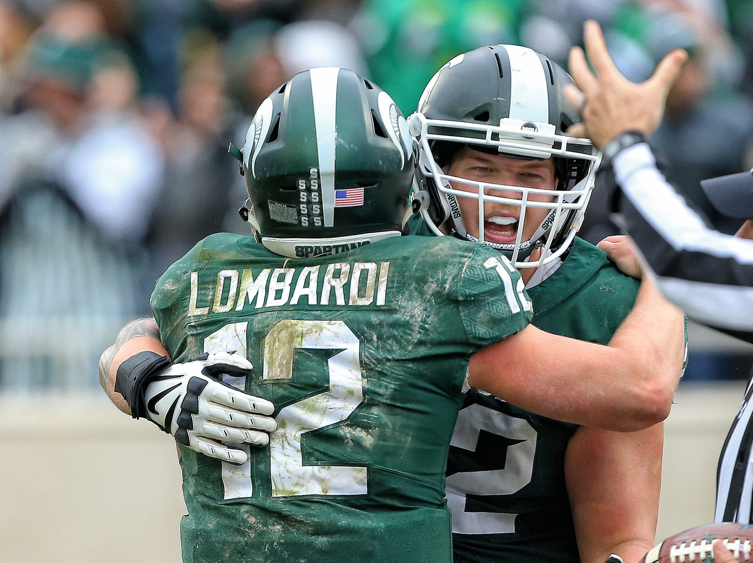 Michigan State Spartans quarterback Rocky Lombardi (12) and offensive tackle Luke Campbell (62) celebrate after a touchdown during the second half against the Purdue Boilermakers at Spartan Stadium.