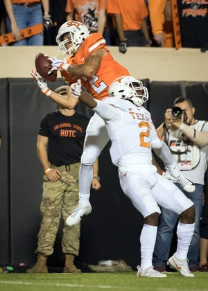 Oklahoma State Cowboys wide receiver Tylan Wallace (2) makes a catch while defended by Texas Longhorns defensive back Brandon Jones (19) during the first half at Boone Pickens Stadium.