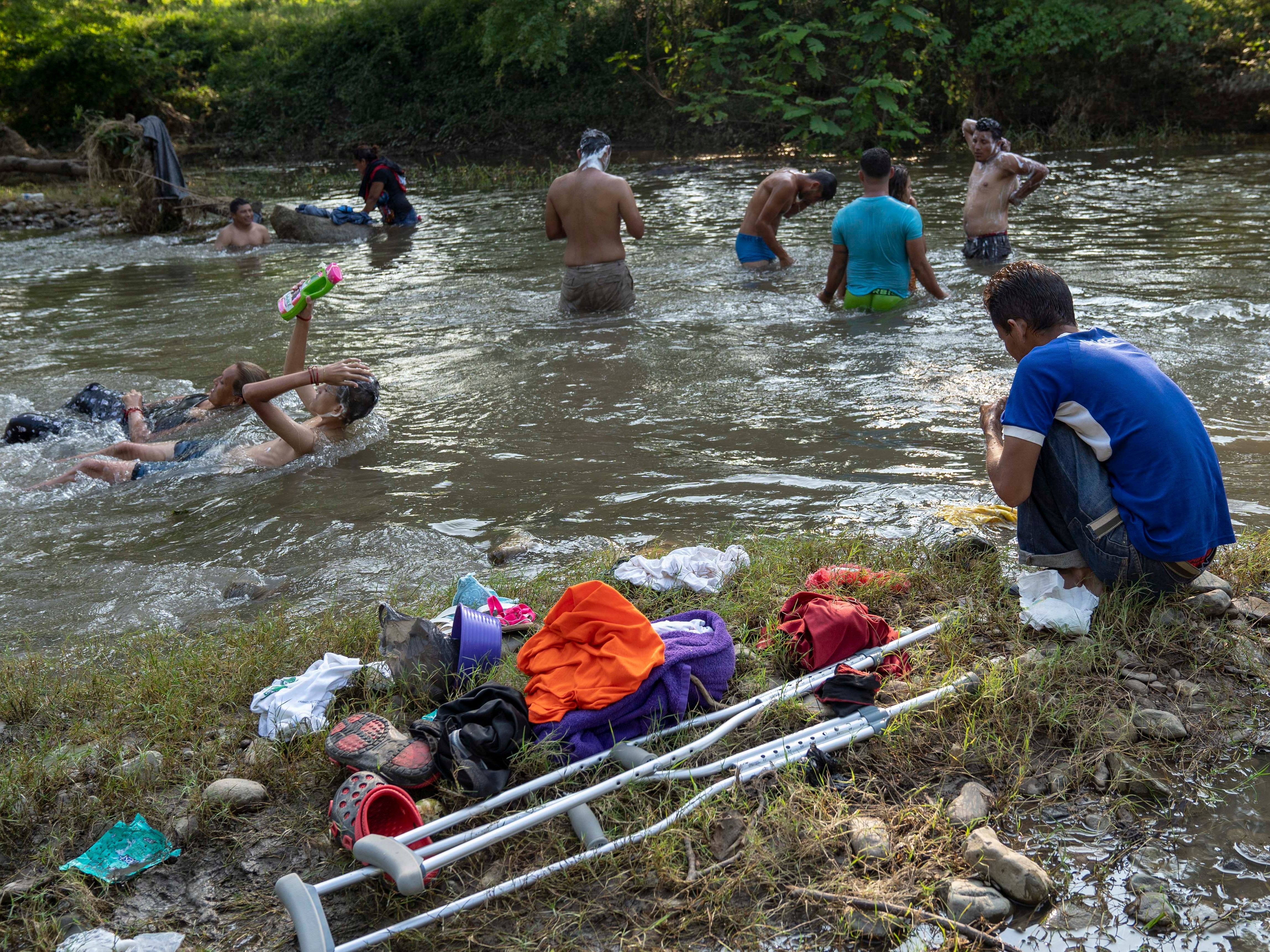 Bathing in the river offers a little relief from a day of walking in the oppressive heat for some of the thousands of migrants in the caravan on Oct. 27, 2018.