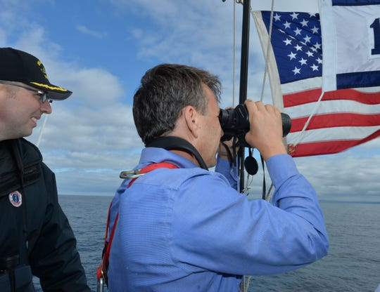 """USS Annapolis Cmdr. John C. Witte, left, looks on as Bryan Alexander keeps a watchful eye out from the """"flying"""" bridge."""