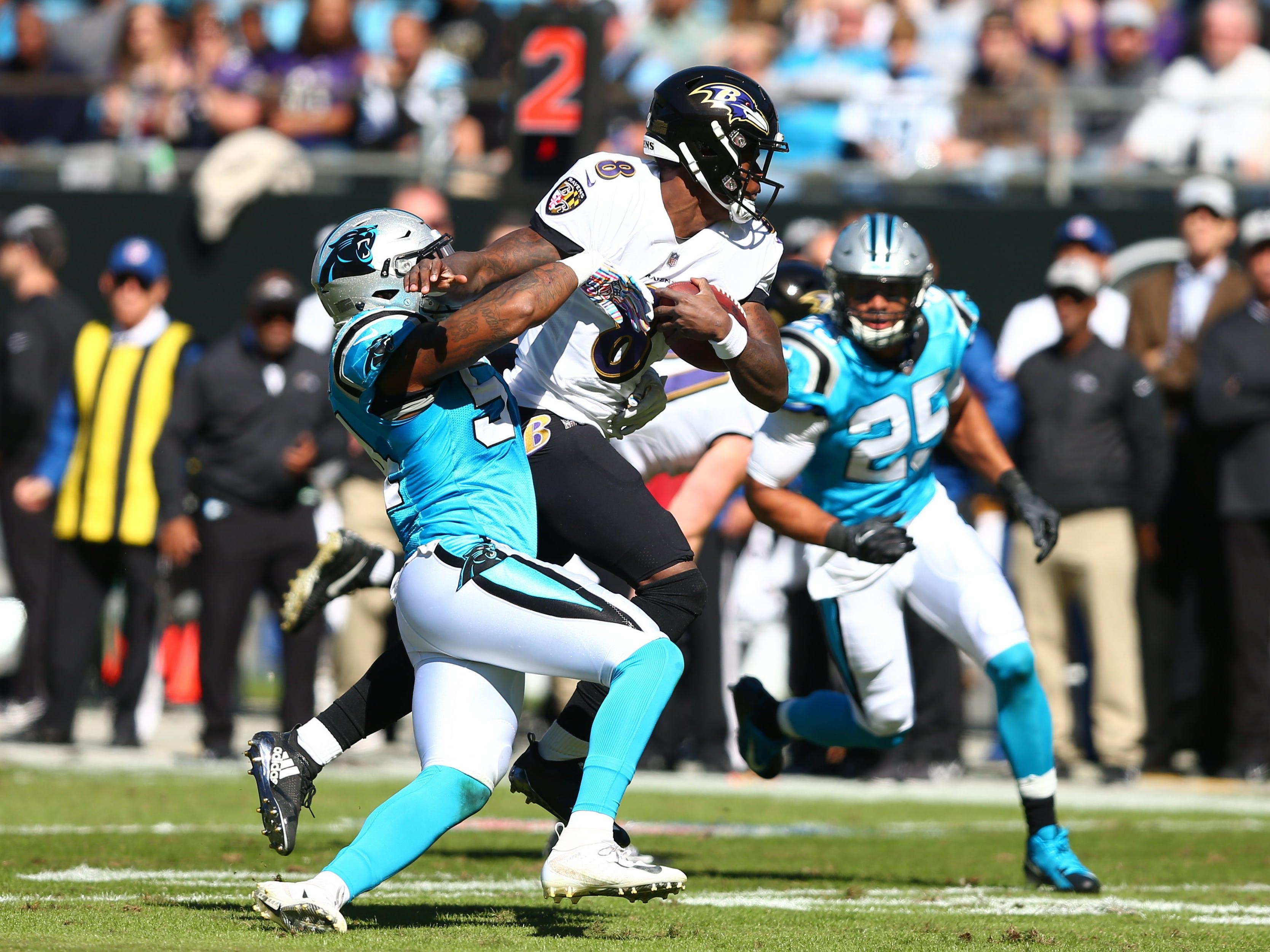 Carolina Panthers linebacker Shaq Green-Thompson (54) wraps up Baltimore Ravens QB Lamar Jackson during the first half at Bank of America Stadium.