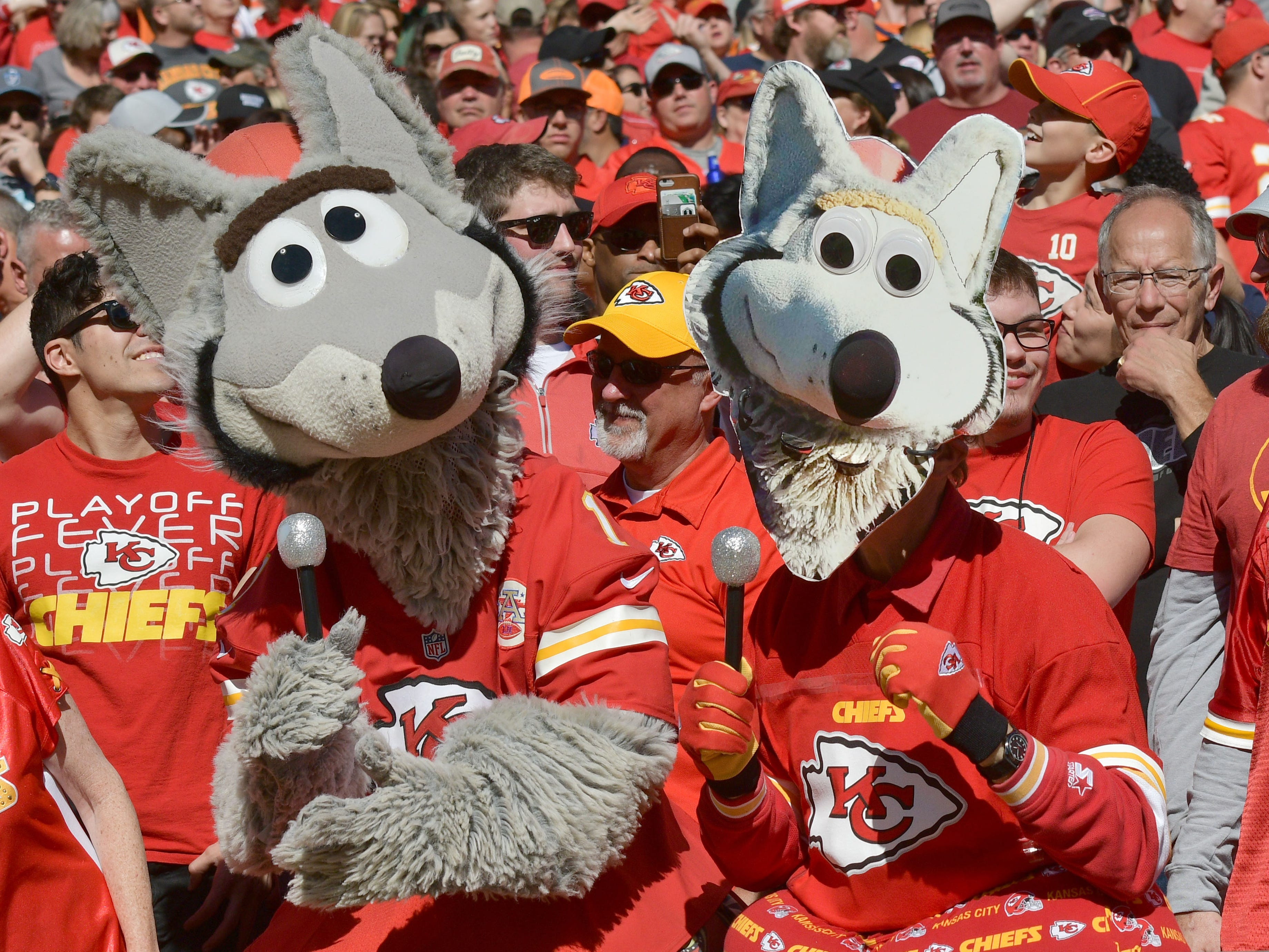 The Kansas City Chiefs mascot KC Wolf sings with a fan in a wolf costume during the second half against the Denver Broncos at Arrowhead Stadium.