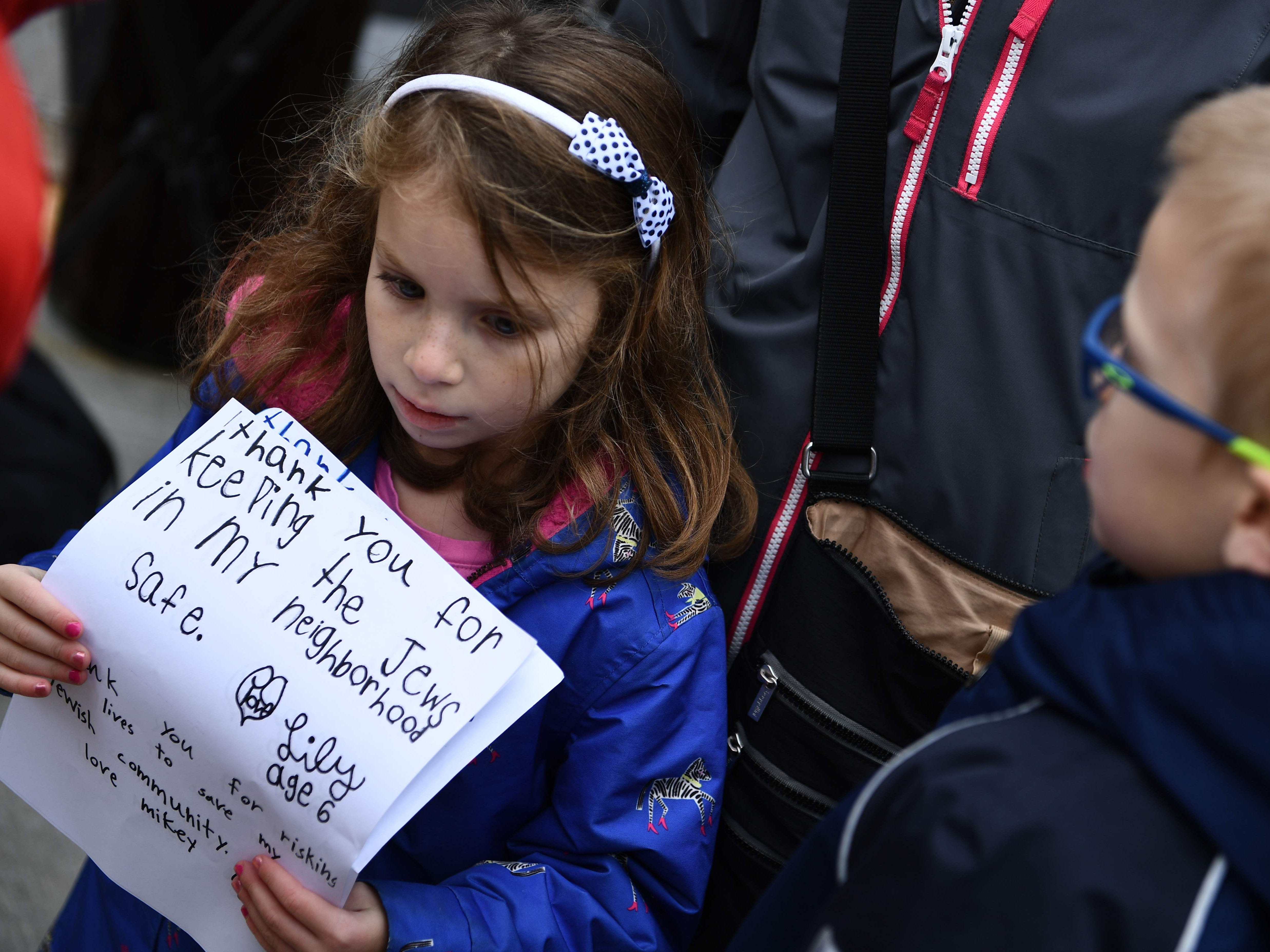 A girl holds thank-you notes on Oct. 28, 2018, outside of the Tree of Life Synagogue in the Squirrel Hill neighborhood of Pittsburgh on Oct. 27, 2018.
