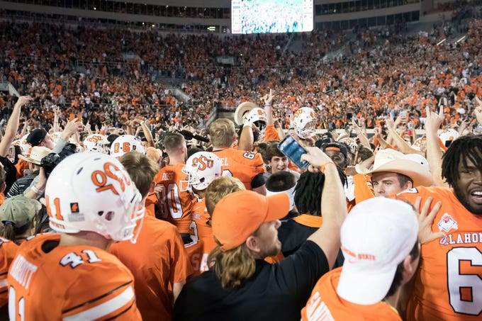 Oklahoma State fans rush the field after the Cowboys defeated No. 7 Texas at Boone Pickens Stadium.