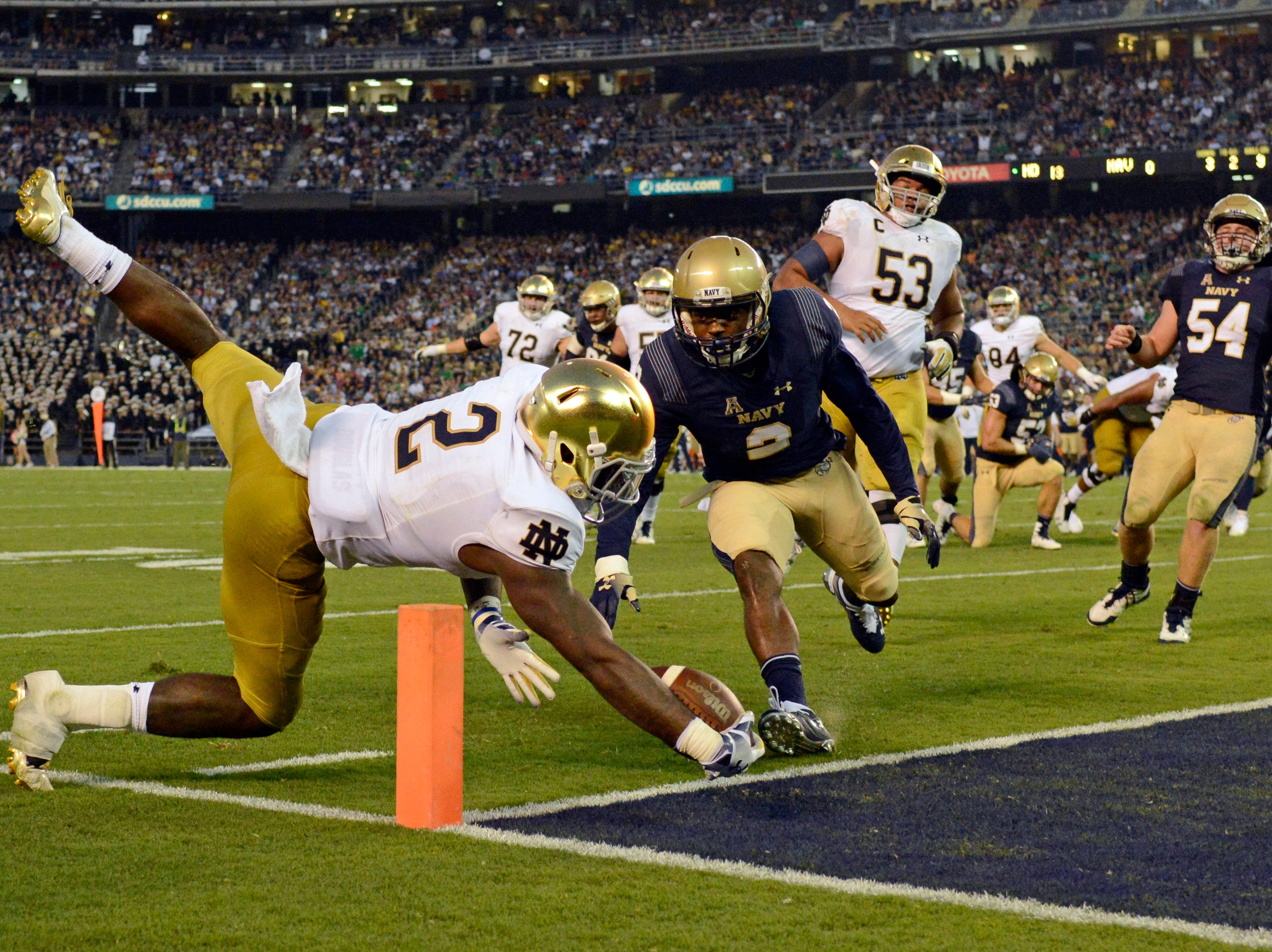 Notre Dame Fighting Irish running back Dexter Williams (left) dives for a touchdown against Navy Midshipmen cornerback Jarid Ryan (right) during the second quarter at SDCCU Stadium.
