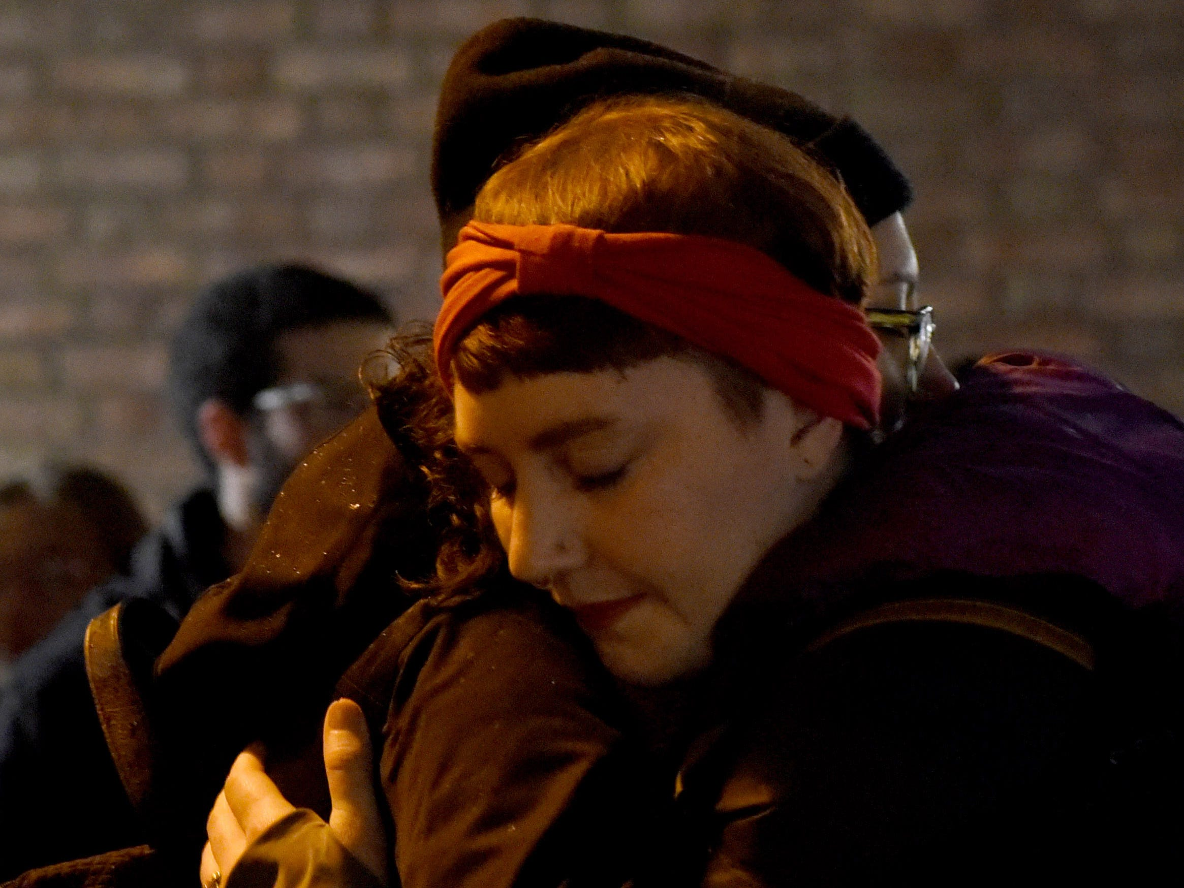Aisling McIntyre, of Pittsburgh, hugs a friend during a vigil during a vigil in the Squirrel Hill neighborhood of Pittsburgh.