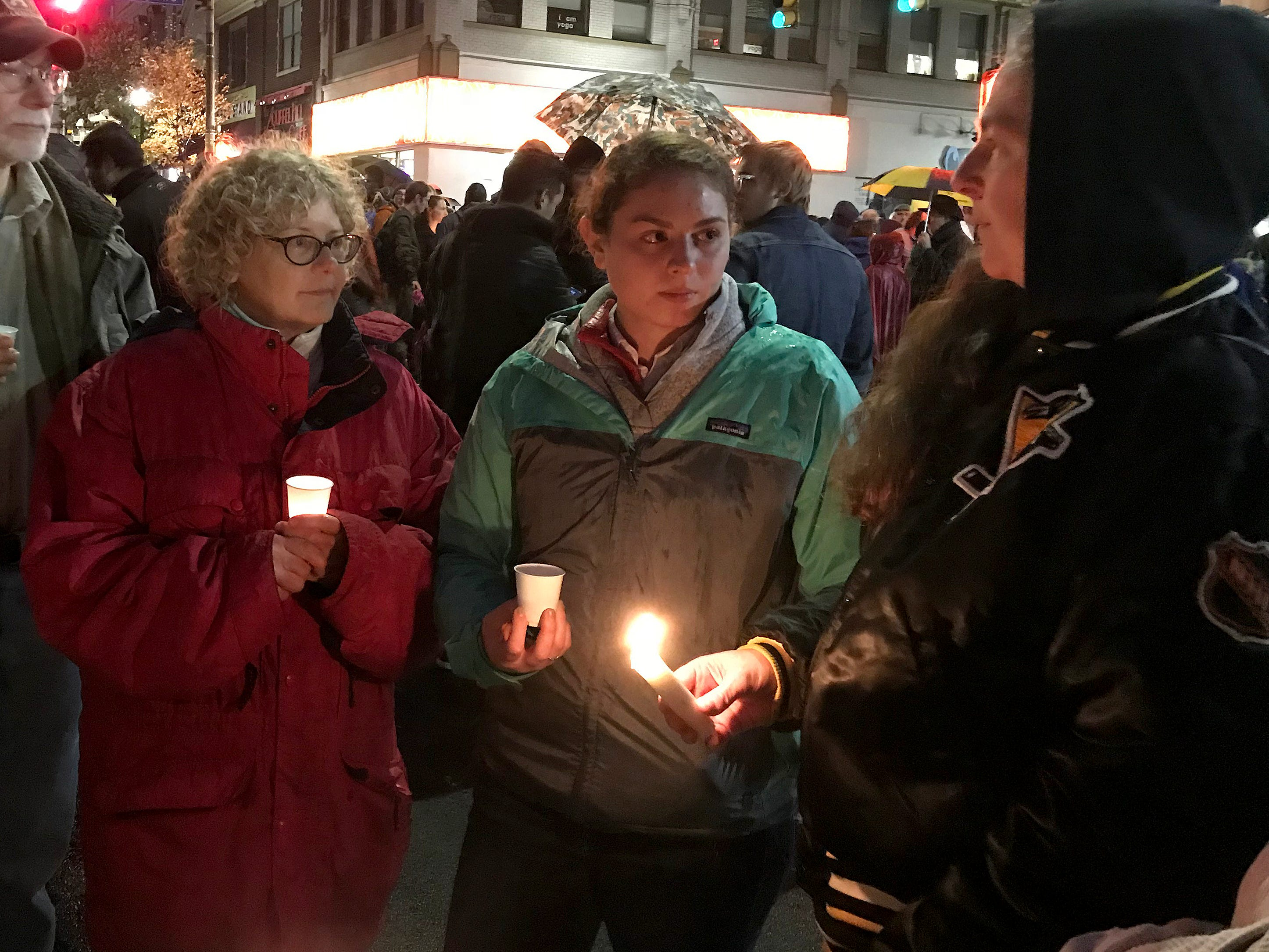 Anne-Marie Silver, left, Mara Silver and Beth Silver,  all members of Congregation Dor Hadash Synagogue, attend a candle-light vigil in the Squirrel Hill neighborhood of Pittsburgh.