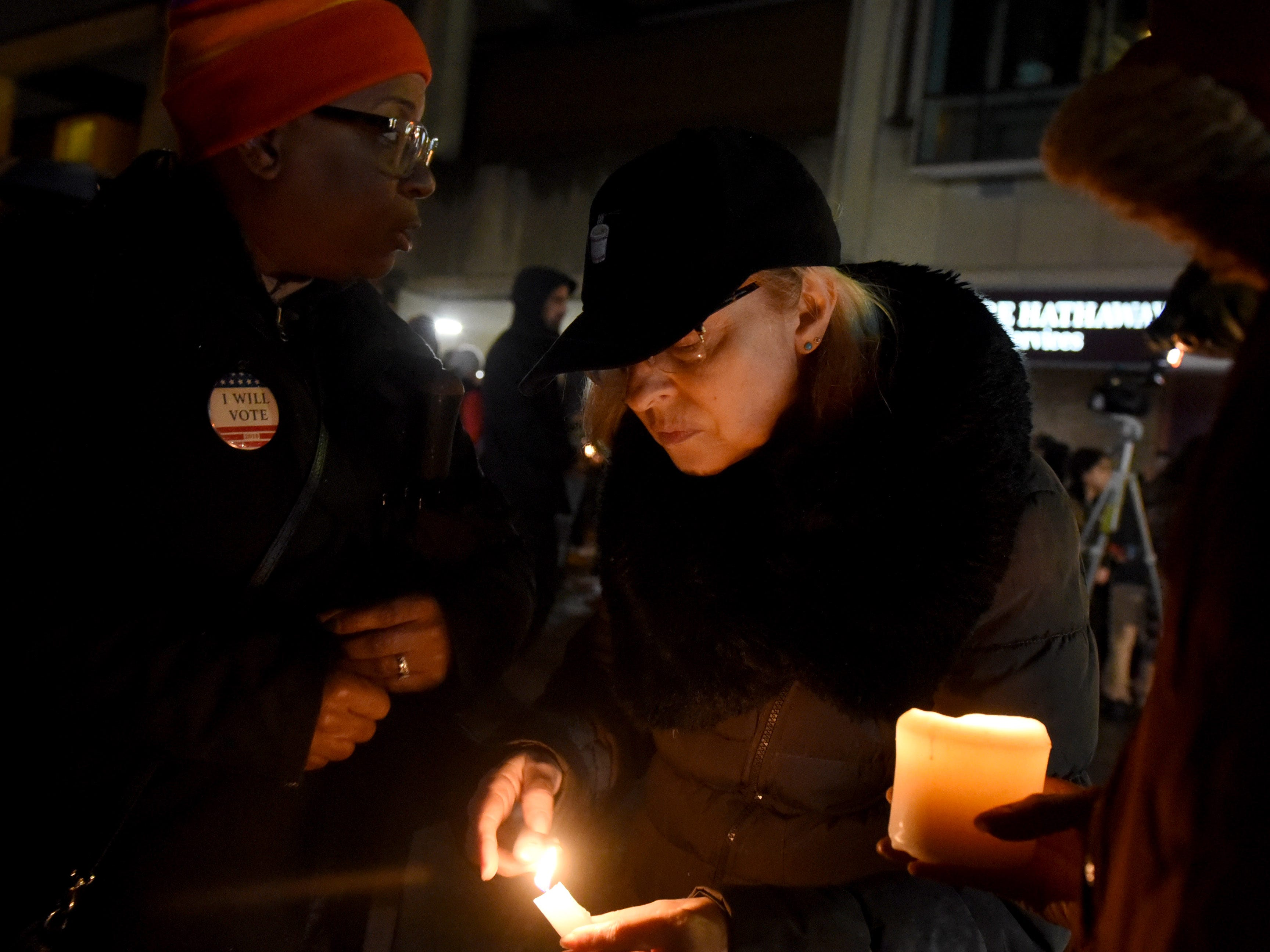 Stephanie Myers and Sally Merar, both of Pittsburgh, try to light candles in a drizzle during a vigil in the Squirrel Hill neighborhood of Pittsburgh.