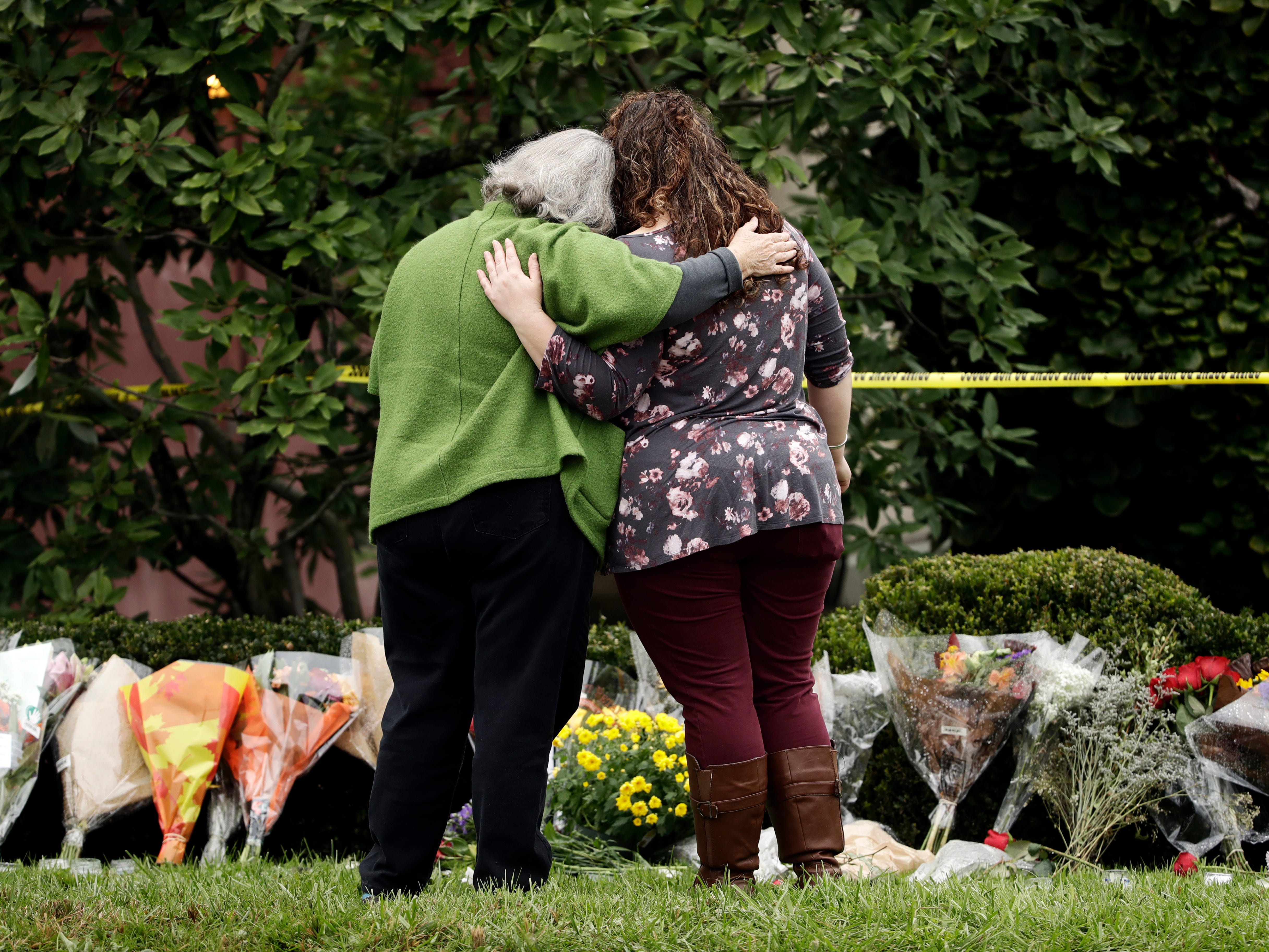 Two people support each other in front of flowers at a makeshift memorial at the Tree of Life Synagogue in Pittsburgh, Sunday, Oct. 28, 2018.