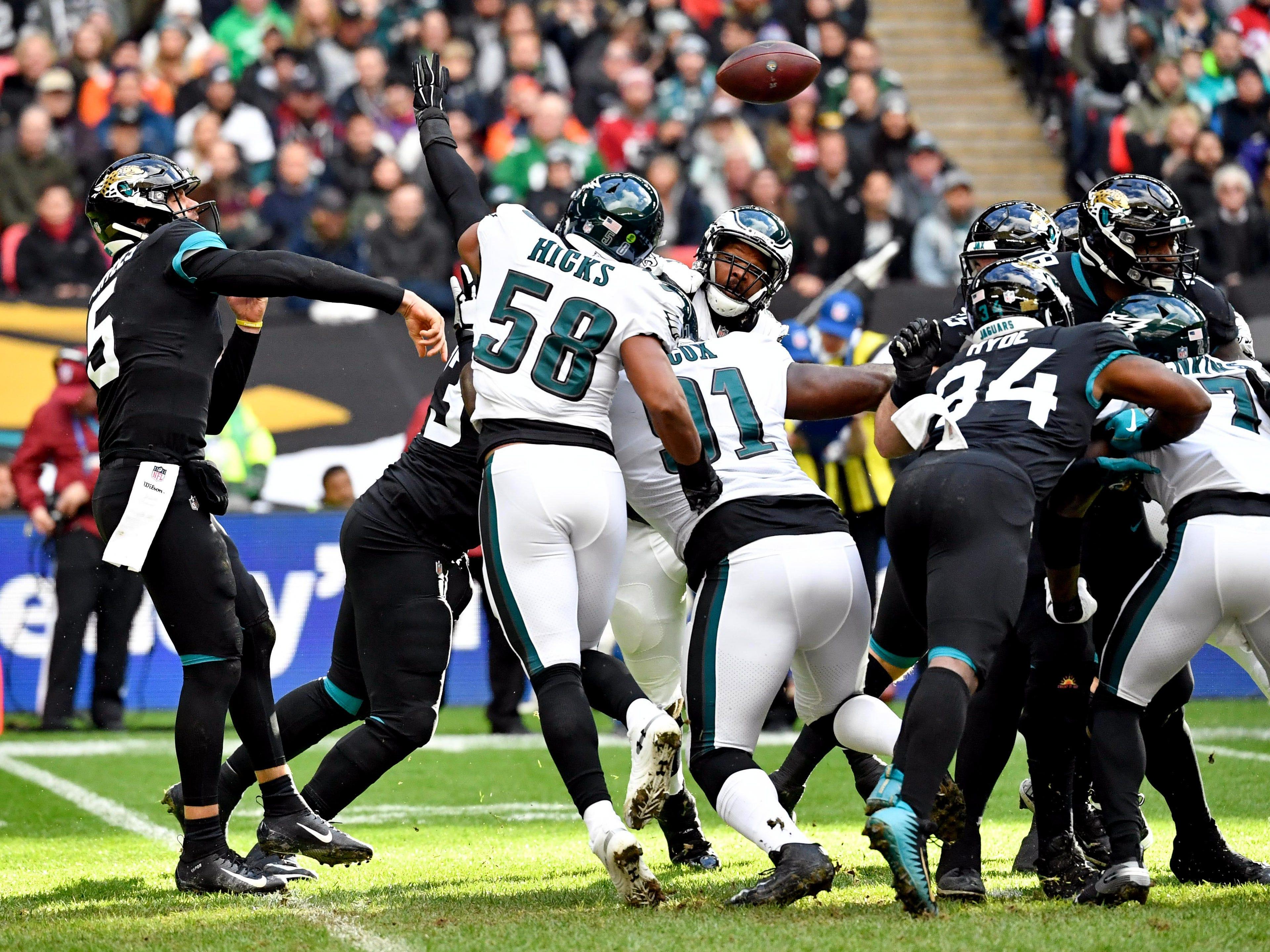 Jacksonville Jaguars quarterback Blake Bortles (5) throws under pressure from Philadelphia Eagles linebacker Jordan Hicks (58) during the first quarter at Wembley Stadium.