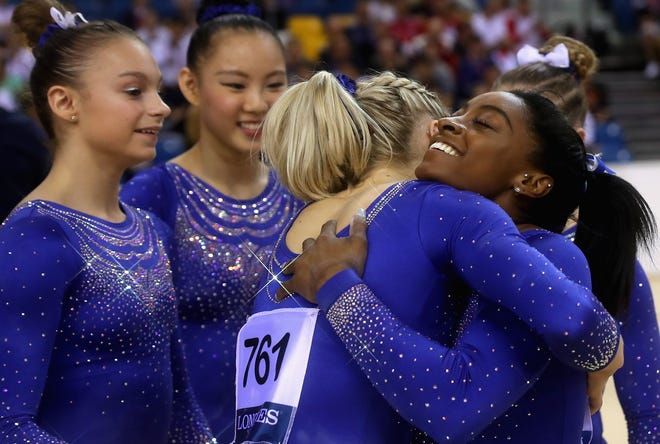 Simone Biles is congratulated by teammates after competing  in the  balance beam qualification during the 2018 FIG Artistic Gymnastics Championships at Aspire Dome on Oct. 27 in Doha, Qatar.