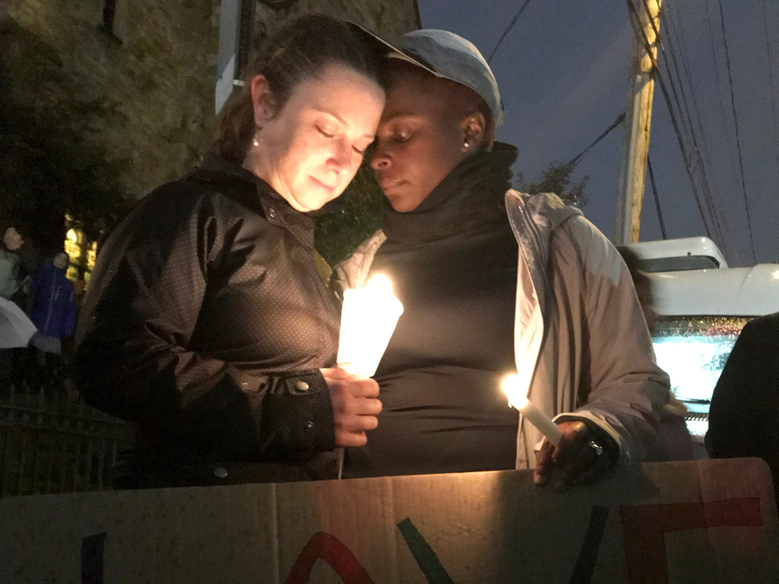 Amira Woodson, 39, left, and Alison Culyba, 39, attend a candle-light vigil in the Squirrel Hill neighborhood of Pittsburgh.
