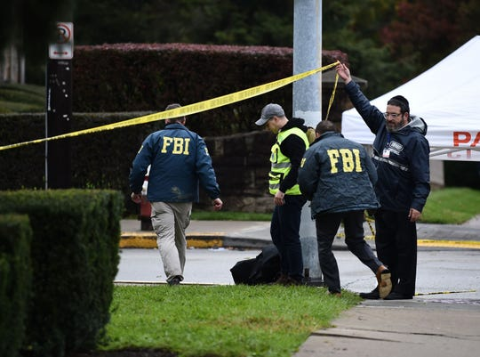 Members of the FBI and others survey the area on Oct. 28, 2018, outside the Tree of Life Synagogue in the Squirrel Hill neighborhood of Pittsburgh on Oct. 27, 2018.