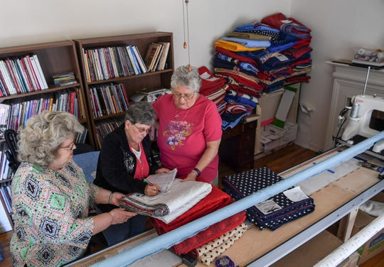 Nancie Doyle, left, of Anderson, watches Doreen Hoegler, center, go through a checklist with Anne Medlin of Anderson during a quilt-making session.