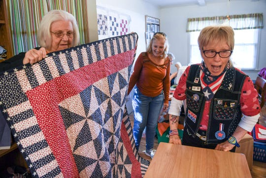 Tina Delk, left, of Anderson holds up a quilt she is making during a gathering with Karen Blomberg, center, and Marion Mockridge, right, of Simpsonville. For the past seven years, Quilts of Valor groups in South Carolina have produced more quilts than those in any other state.