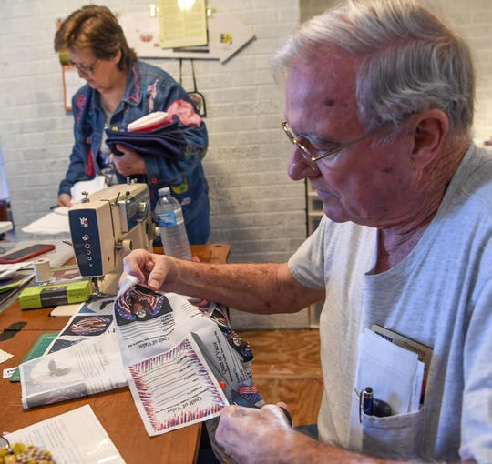 Tommy Forrest, himself a recipient of a Quilt of Valor, now helps make them himself. Here he prepares to cut labels to sew on quilts with other volunteers during a session in Anderson.