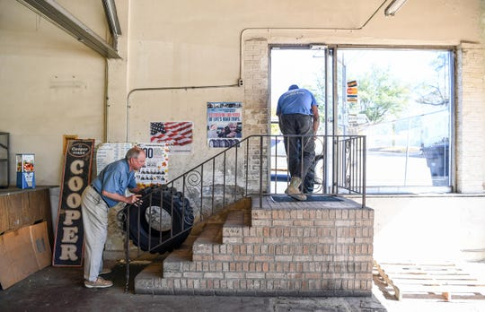 Don Cox, left, who took over as owner of the family owned Cox Oil Co, Inc. of 61 years, helps customer Kenell Ward, right, of Anderson load the two tires he sold him at the store on East Calhoun Street in Anderson on Monday.