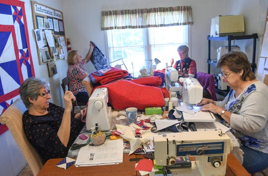 Deborah Sheriff, left, hand-sews a label onto a quilt she made as other volunteers work on quilts for the Anderson County Quilts of Valor chapter.