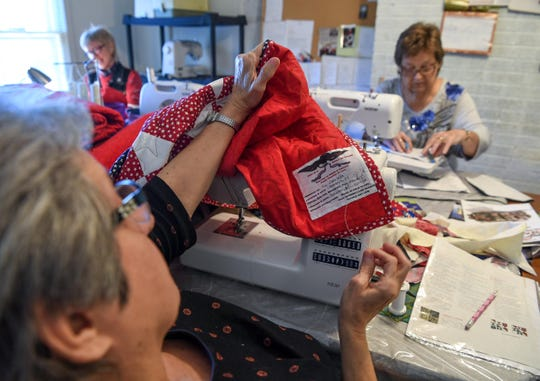 Deborah Sheriff, left, works on a quilt bound for a veteran in Connecticut as part of Quilts of Valor.