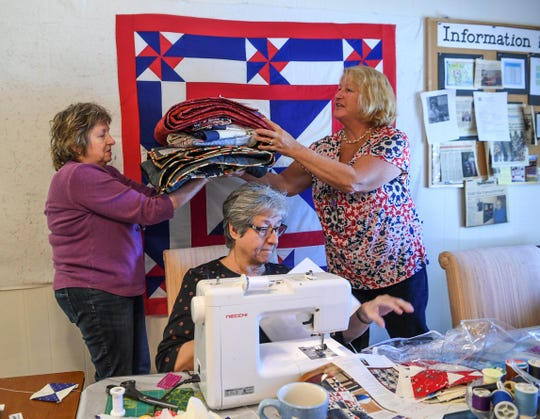 Debbie Smith, left, takes a stack of quilts from Meg Stewart, right, of Fair Play, while Deborah Sheriff, center, sews during a quilting session in Anderson.