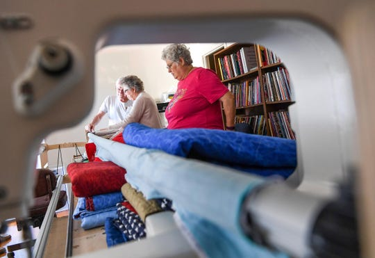 Tommy Forrest, left, works on quilts with Monte Ruble, center, and Anne Medlin, right, of Anderson. The Anderson group is one of the most active Quilts of Valor chapters in the state.