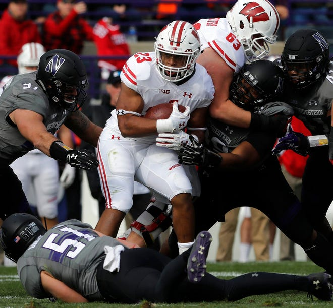 Wisconsin running back Jonathan Taylor (23) is tackled by Northwestern defenders during the first half of an NCAA college football game in Evanston, Ill., Saturday, Oct. 27, 2018. (AP Photo/Nam Y. Huh)