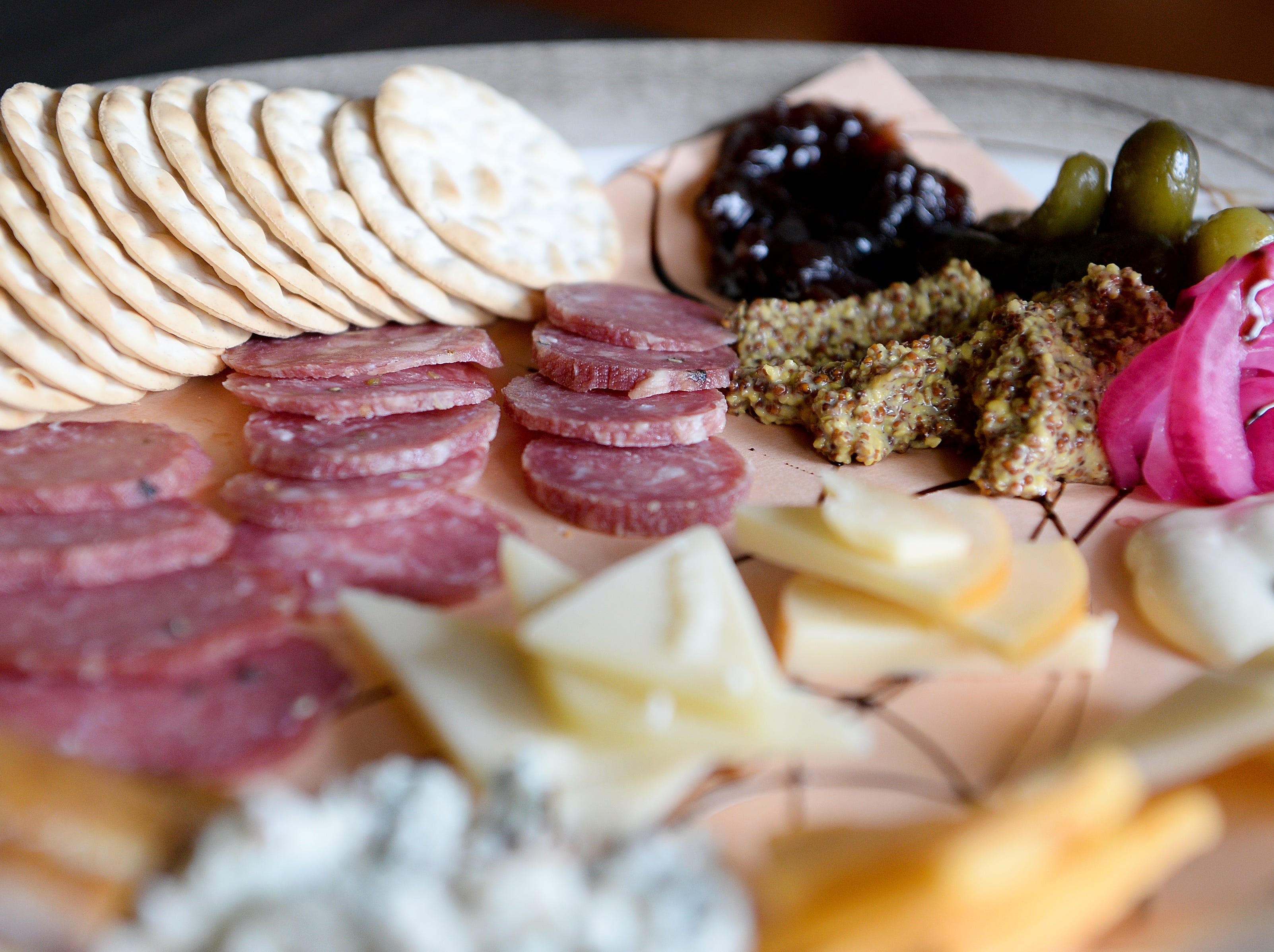 The Jumbo Plate at Little Jumbo combines their cheese plate with their charcuterie board bringing you a selection of five assorted cheeses, a selection of four Hickory Nut Gap farm meats, Sunburst Farms smoked trout and is served with olives, house pickled red onions, gherkins, mustard, and onion jam.