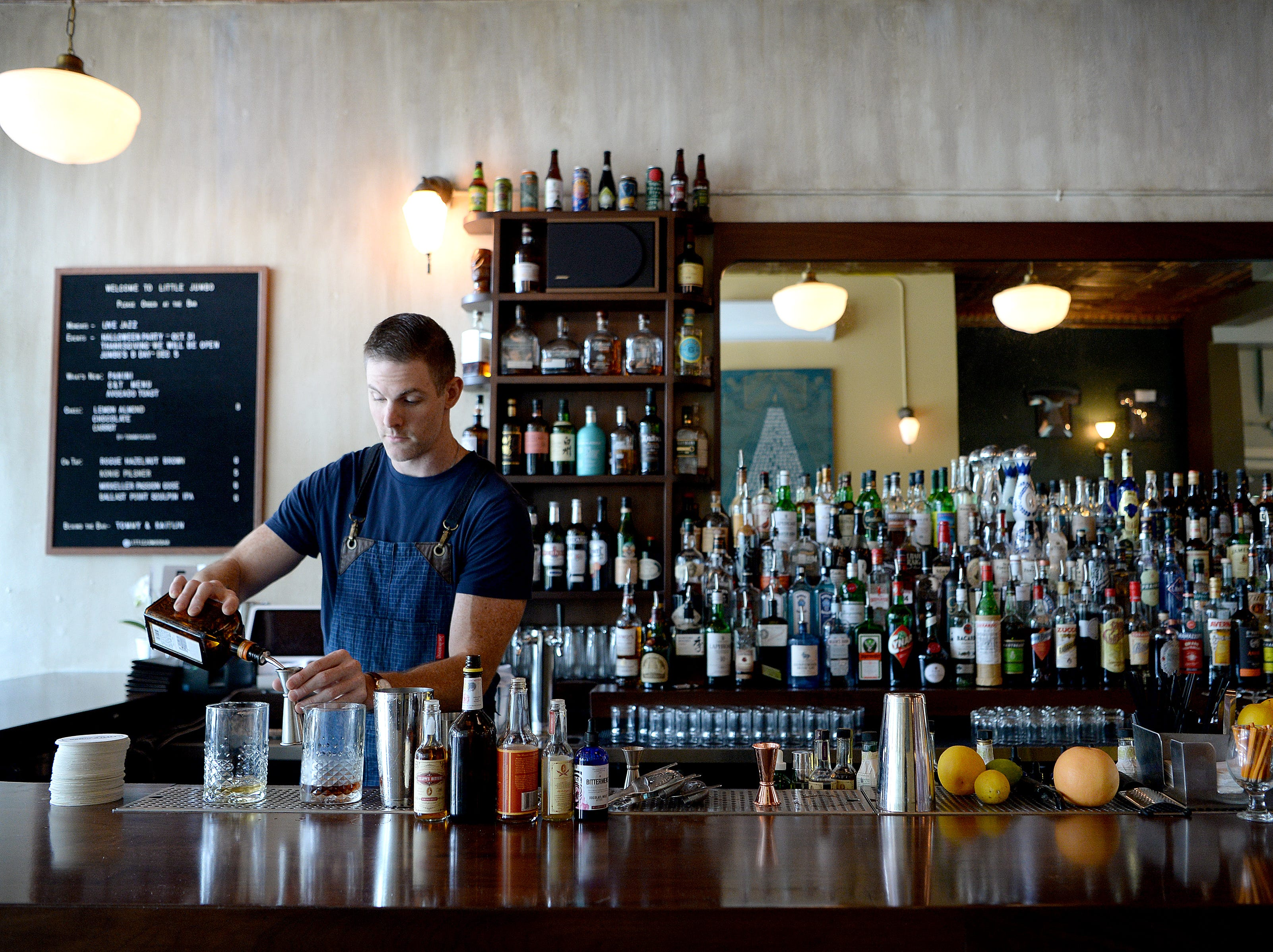 Tommy Schnell makes up a batch of drinks from behind the bar at Little Jumbo on Oct. 26, 2018.