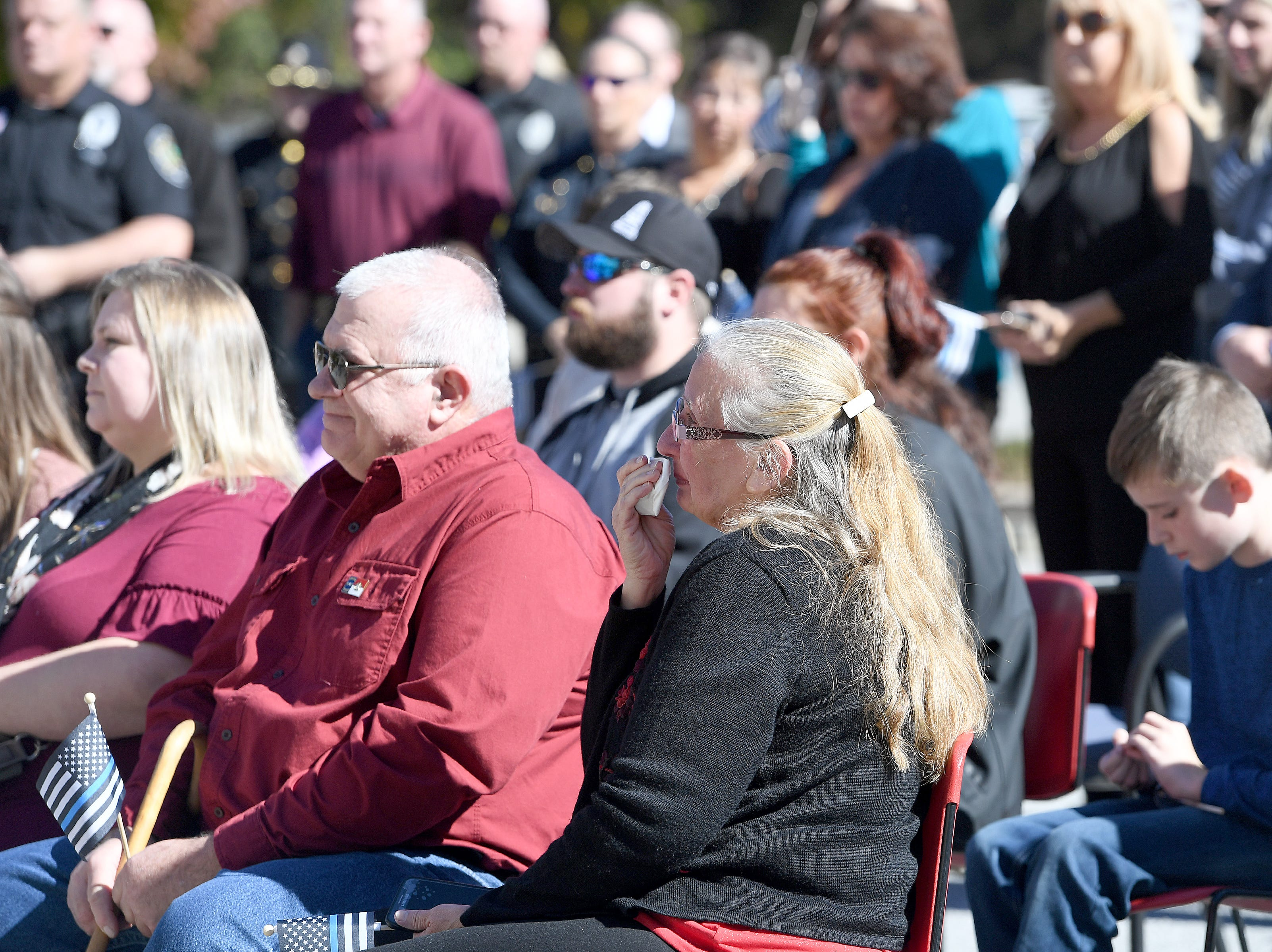 Robert Bingaman's mother, Donna, right, wipes her face during a ceremony to dedicate a portion of Old Haywood Road to the Asheville police officer at the Traffic Safety Office on the five-year-anniversary of his death on Oct. 29, 2018.