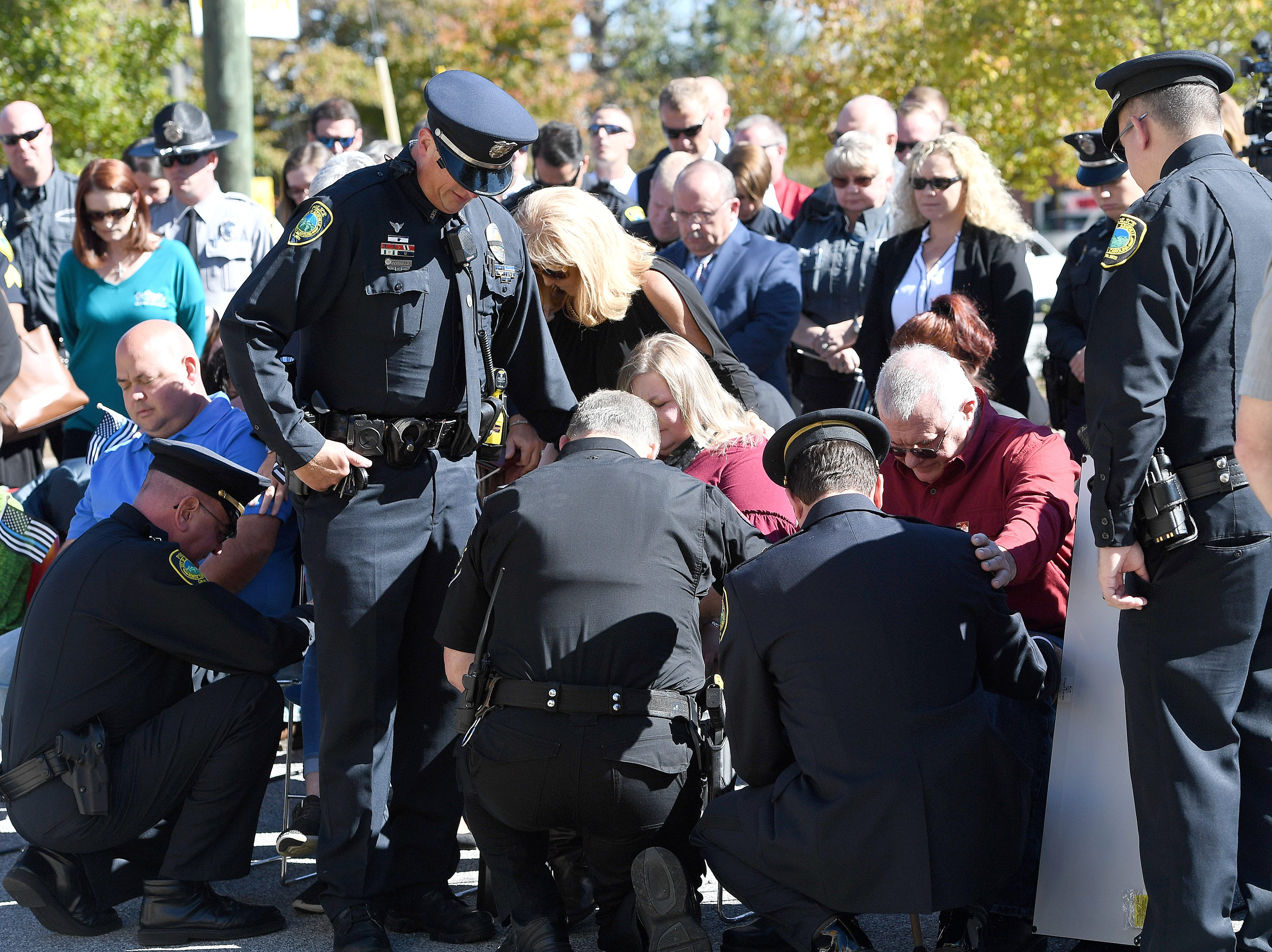 Attendees surround the family of Robert Bingaman for five minutes of silence honoring the five-year-anniversary of the Asheville police officer's death during a ceremony to dedicate a portion of Old Haywood Road to Bingaman at the Traffic Safety Office on Oct. 29, 2018. A call was placed on the police scanner asking on-duty officers for a moment of silence as well.