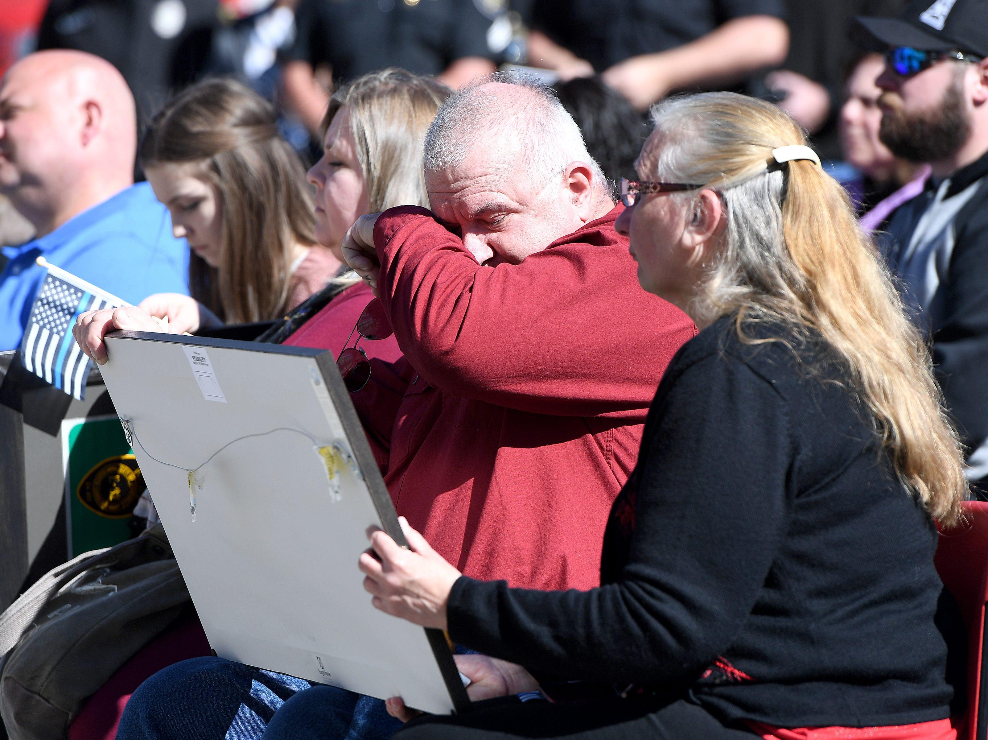 Robert Bingaman's father, Robert Allen Bingaman, wipes his face after he and his wife, Donna, were presented with a framed sign like the one dedicating a portion of Old Haywood Road to the Asheville police officer at the Traffic Safety Office on the five-year-anniversary of his death on Oct. 29, 2018.
